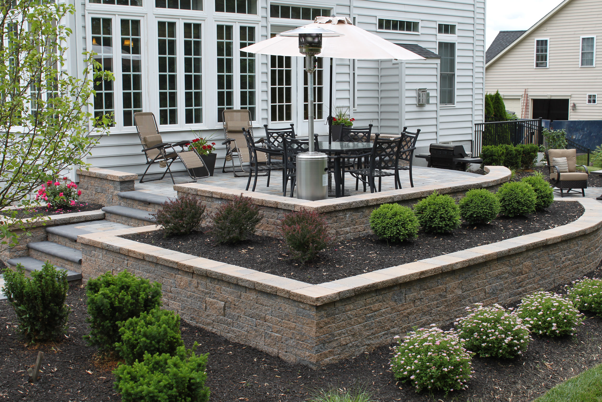raised-patio-with-pavers by R & R Landscape Design